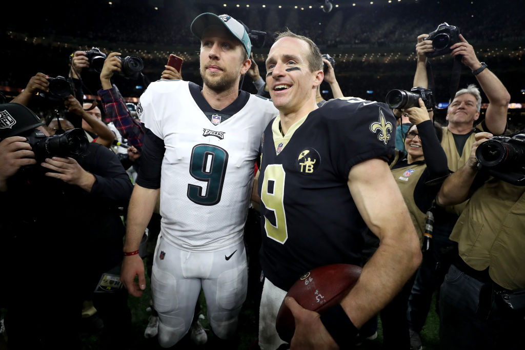 Nick Foles of the Philadelphia Eagles meets with Drew Brees of the New Orleans Saints on the field