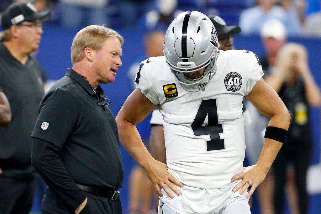 Head coach Jon Gruden of the Oakland Raiders talks with Derek Carr