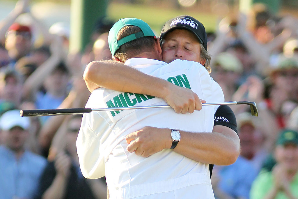 Phil Mickelson hugs his caddie Jim Mackay after winning the 2010 Masters Tournament