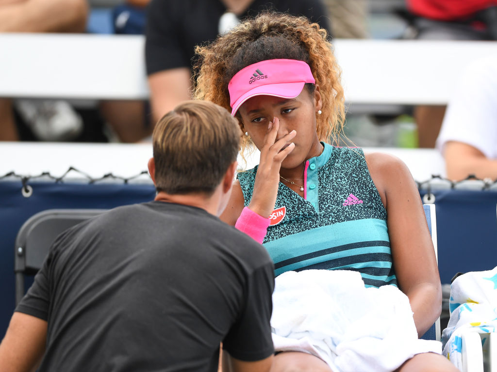 A professional tennis coach talks to Naomi Osaka on the bench.