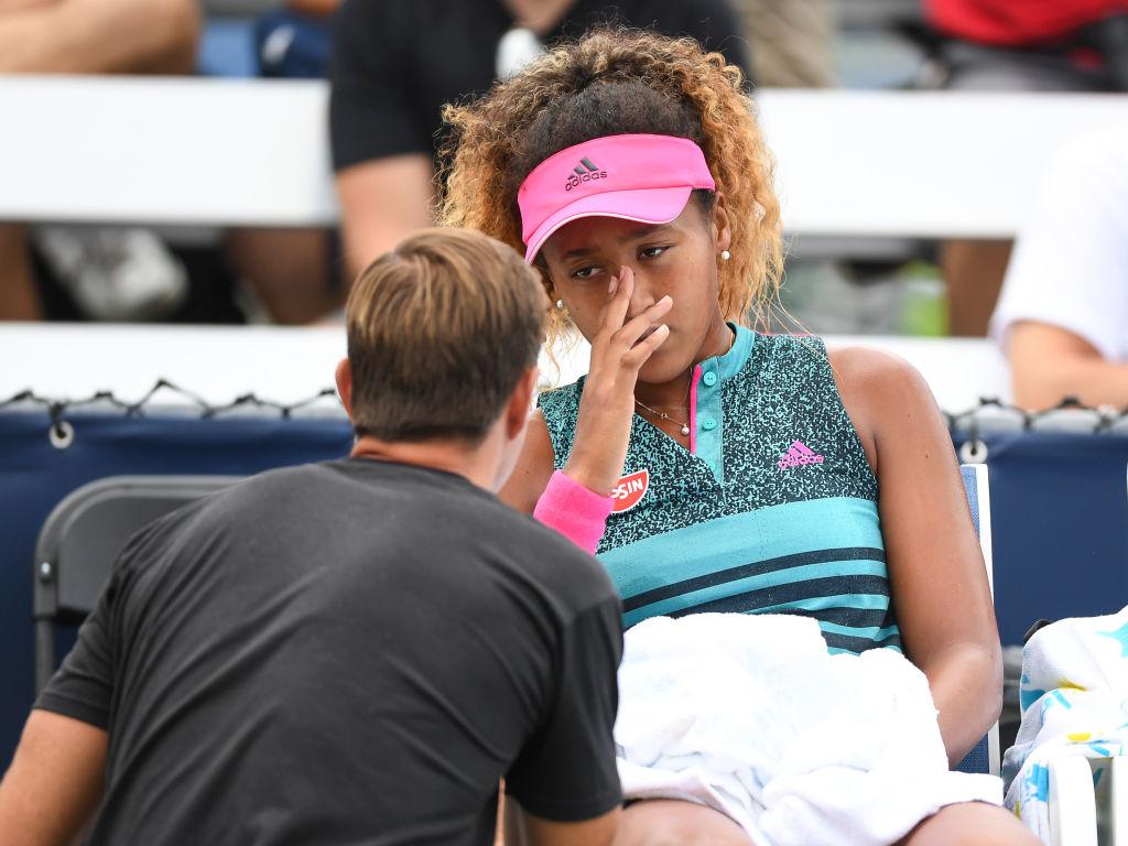 A professional tennis coach talks to Naomi Osaka on the bench.