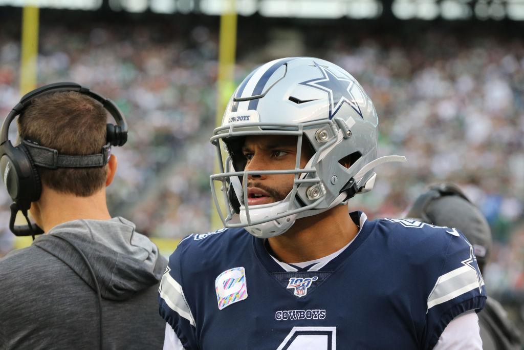 Quarterback Dak Prescott of the Dallas Cowboys follows the action from the sideline