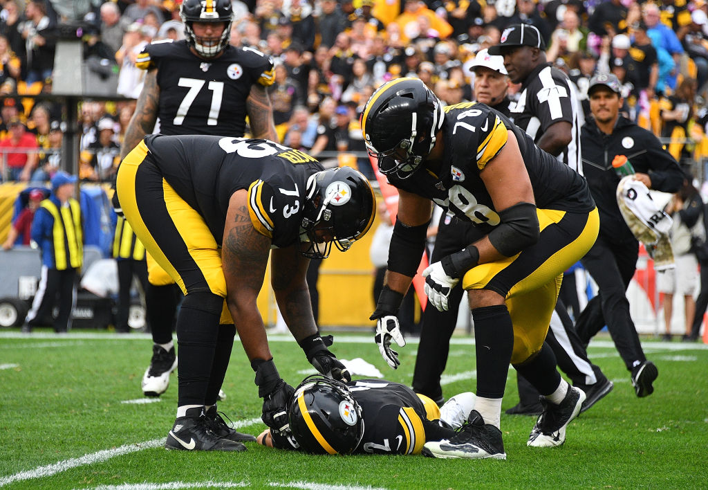 Ramon Foster and Alejandro Villanueva check on Mason Rudolph of the Pittsburgh Steelers after he is injured