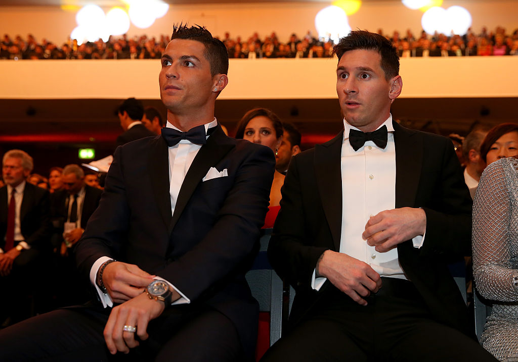 Cristiano Ronaldo sits with Lionel Messi at an award presentation.