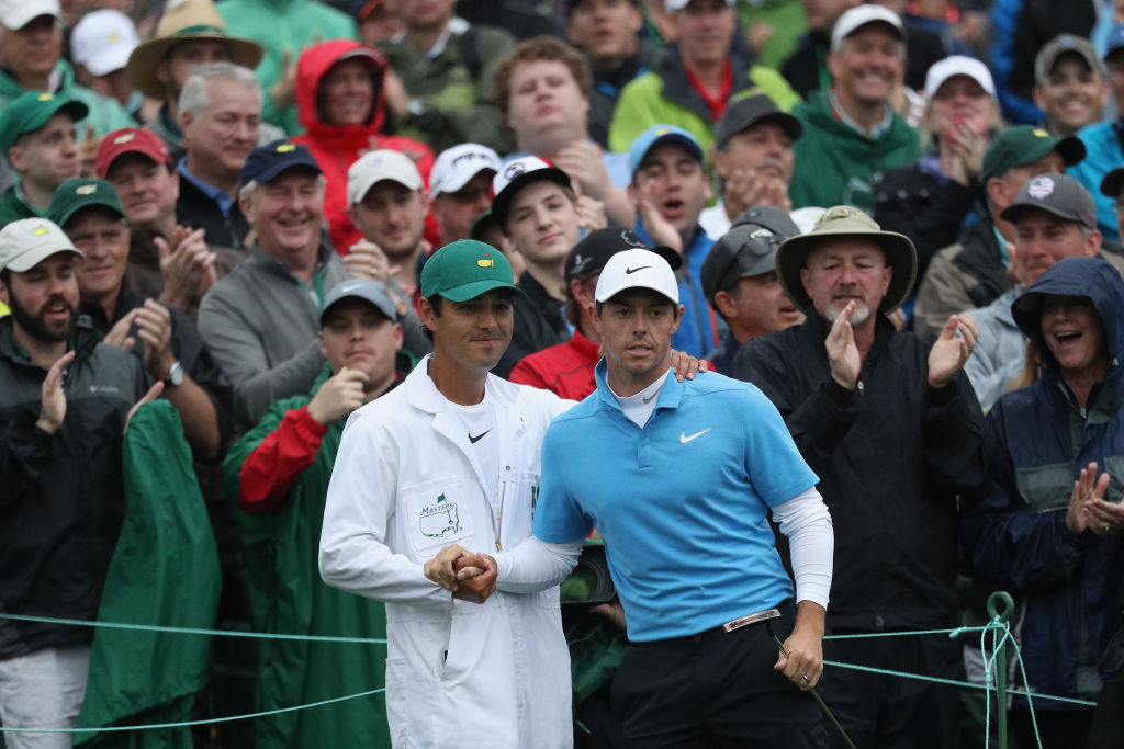 Rory McIlroy of Northern Ireland and caddie Harry Diamond shake hands on the 18th green of the 2018 Masters