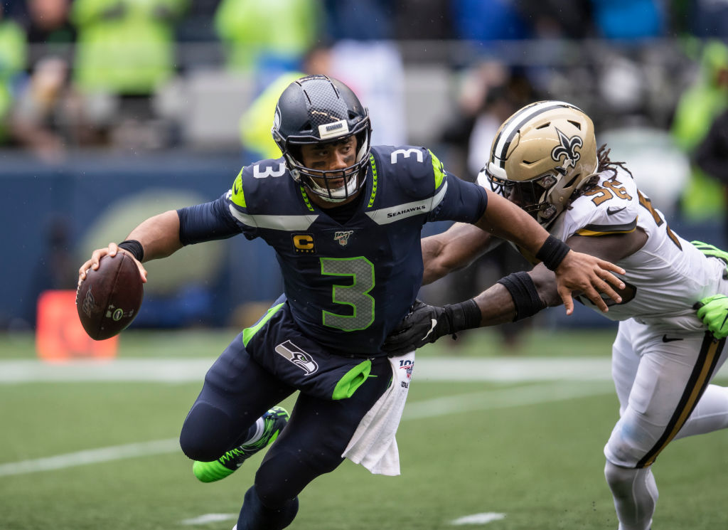 Super Bowl champion Russell Wilson avoids a tackle in an NFL game.
