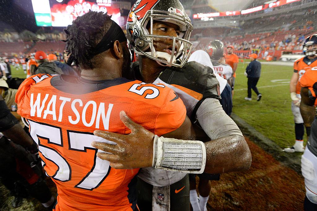 Tampa Bay Buccaneers quarterback Jameis Winston gets a hug from Denver Broncos linebacker Dekoda Watson
