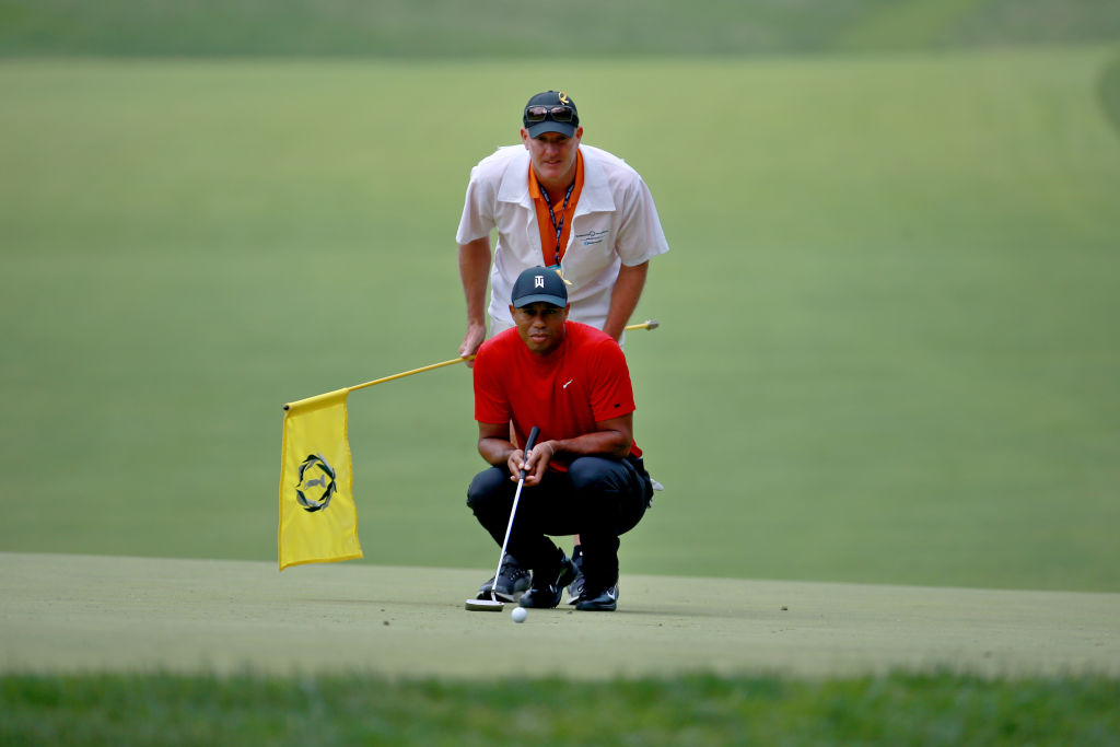 Tiger Woods lines up a putt with his caddie Joe LaCava