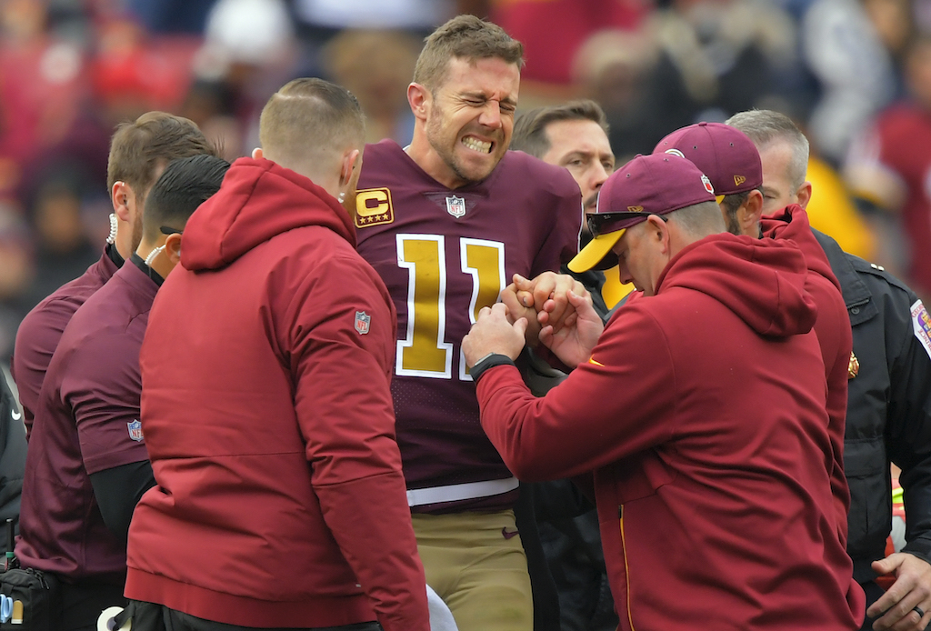 Washington Redskins quarterback Alex Smith grimaces after suffering an lower leg injury