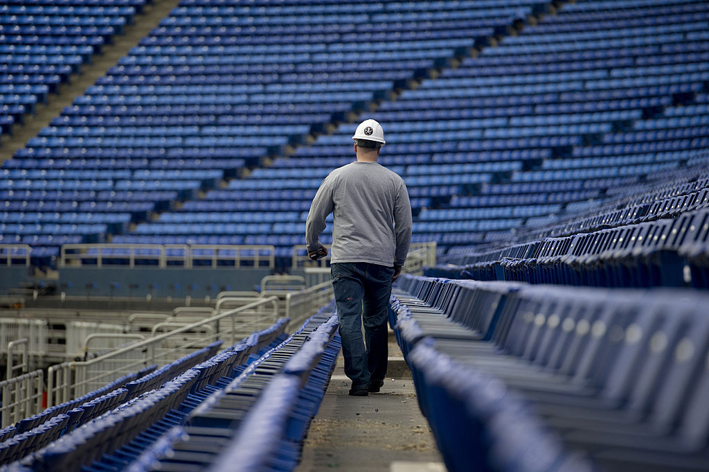 A worker walks along a row of seating during the demolition process at the Metrodome in Minneapolis