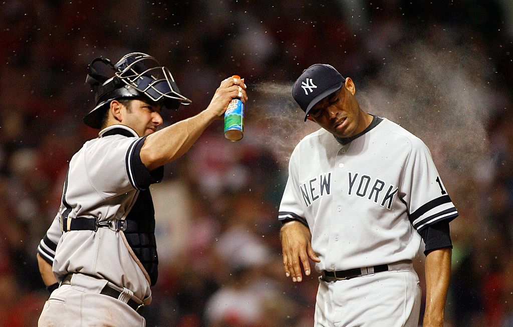 Yankees catcher Jorge Posada spraying pitcher Mariano Rivera with bug spray