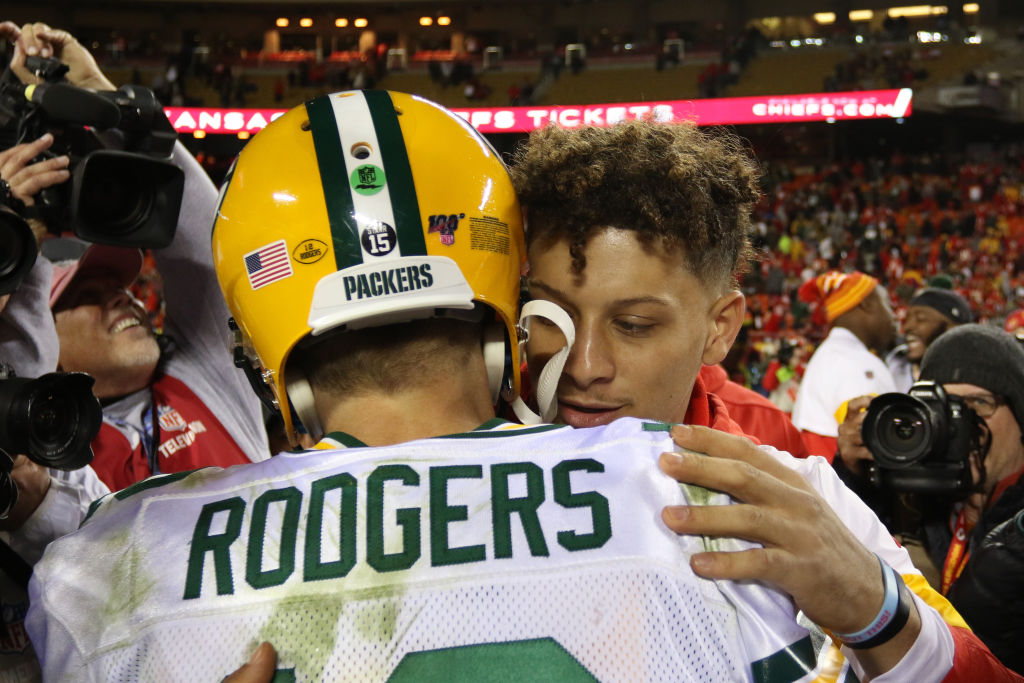 Quarterbacks Aaron Rodgers and Patrick Mahomes embrace at midfield after a game.