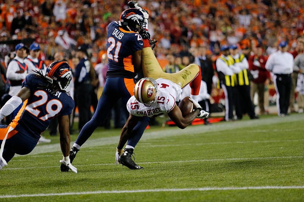 Aqib Talib tackling Michael Crabtree during an NFL game.
