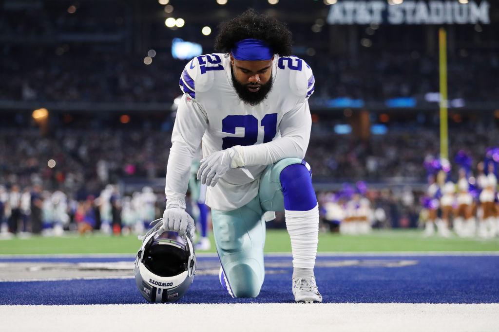 Dallas Cowboys running back Ezekiel Elliott takes a knee before a game.