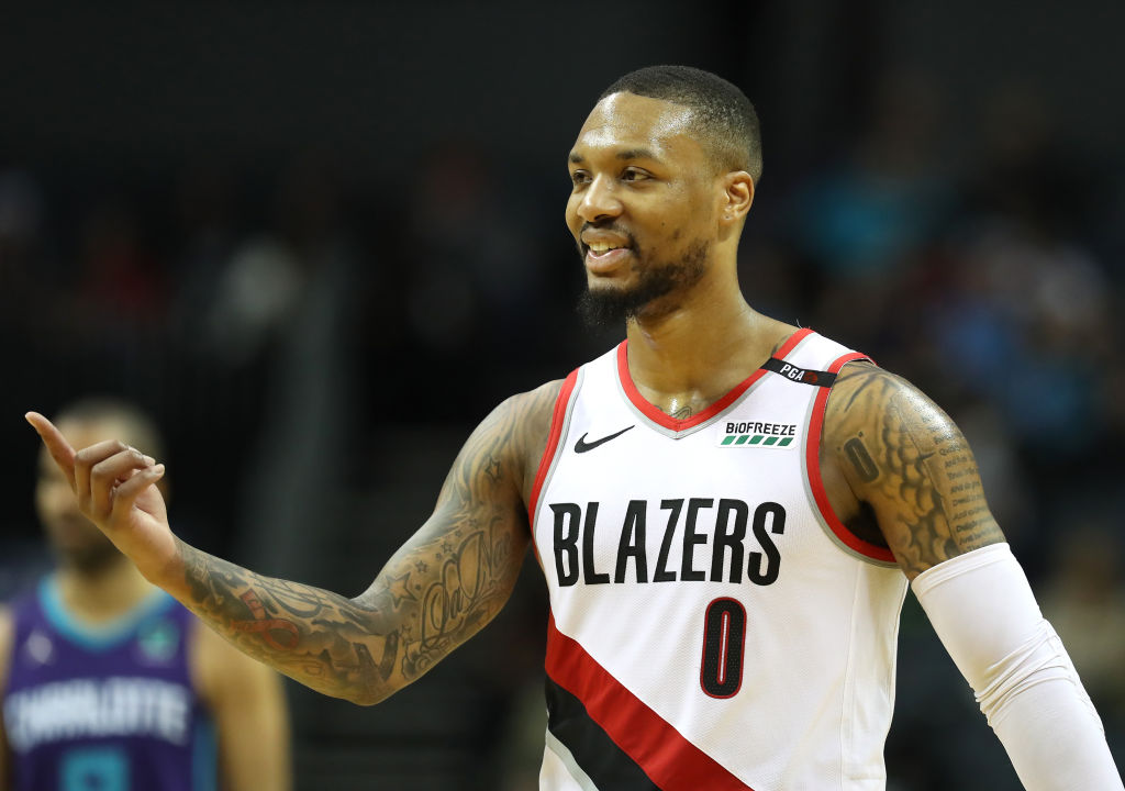 Portland Trail Blazers' guard Damian Lillard laughing on the court.