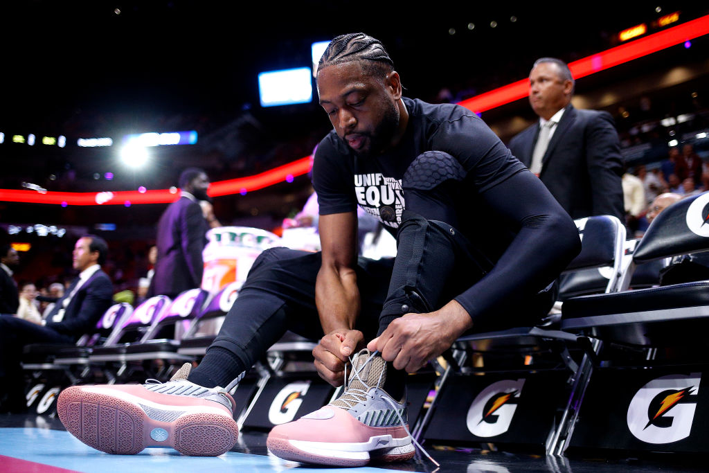 NBA star, Dwyane Wade tying up his shoes before a game