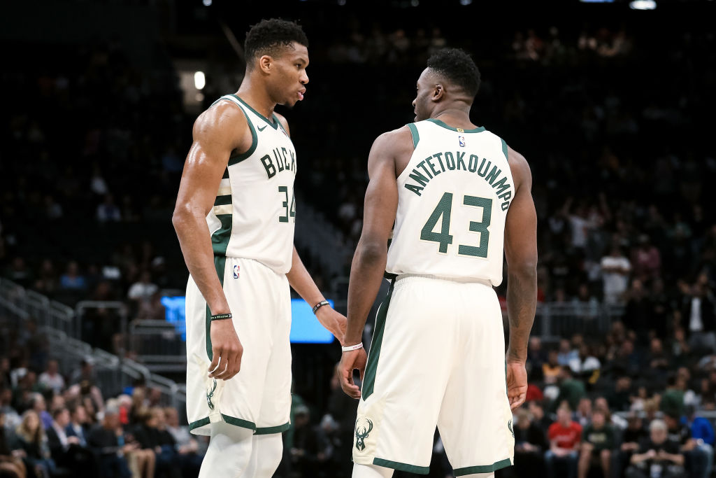 Giannis and Thanasis Antetokounmpo stand on the court together.