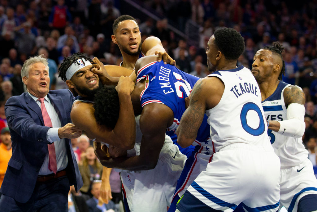 Joel Embiid of the Philadelphia 76ers gets in a fight with Karl-Anthony Towns of the Minnesota Timberwolves as head coach Brett Brown and Ben Simmons try to break them apart