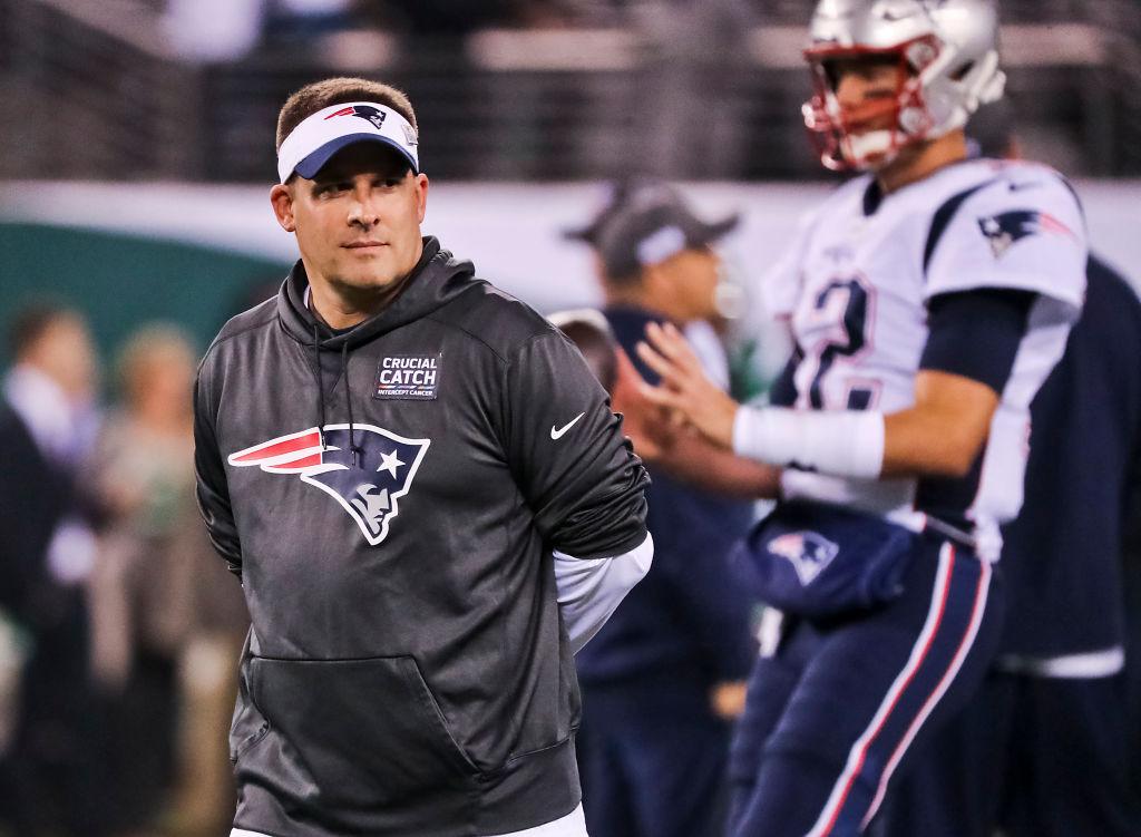 New England Patriots offensive coordinator Josh McDaniels standing with Tom Brady