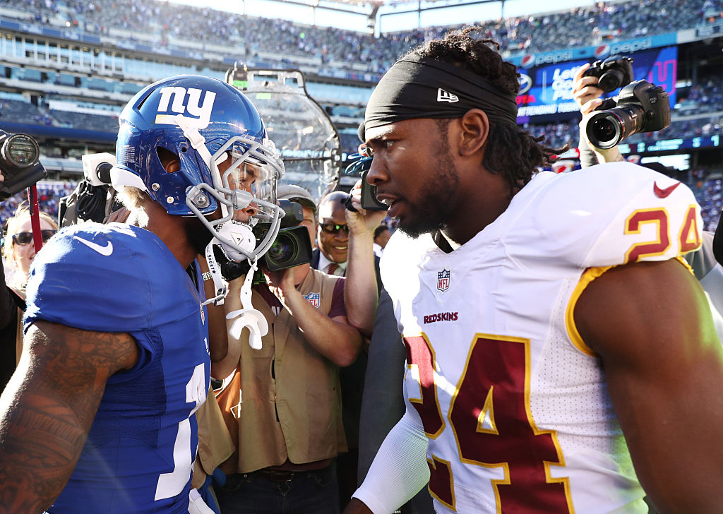 Josh Norman and Odell Beckham talk trash at midfield after a game.