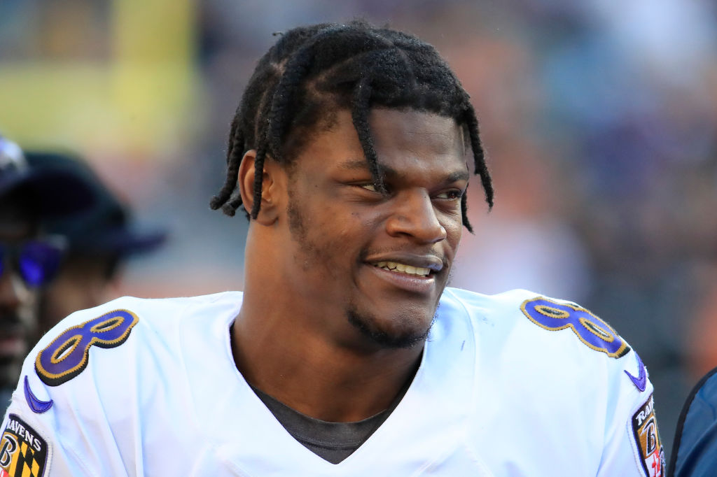 Ravens' quarterback, Lamar Jackson smiles as he walks off the field.