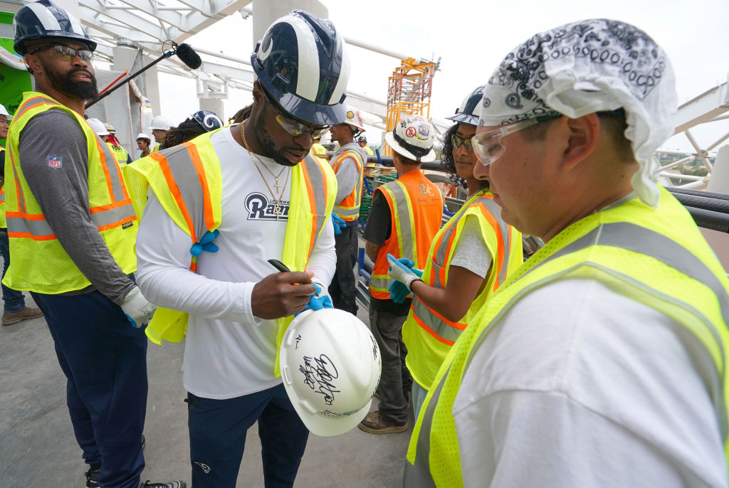 Los Angeles Rams rookie Nick Scott autographs the helmet of construction worker Mathew Renteria as they tour the new LA Stadium construction site