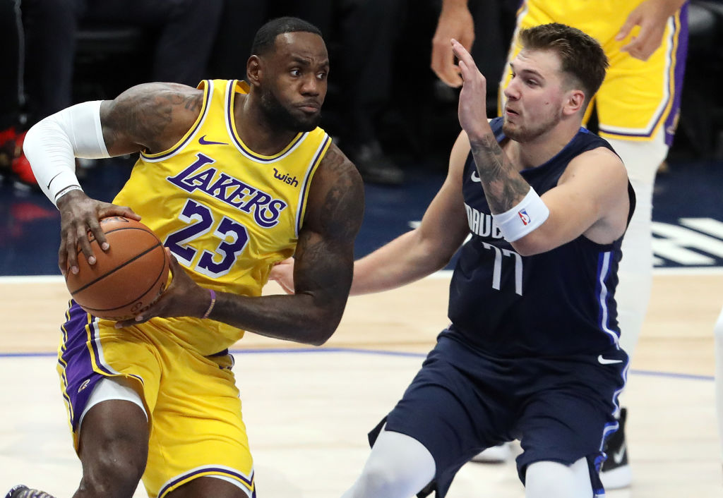 LeBron James #23 of the Los Angeles Lakers dribbles the ball against Luka Doncic #77 of the Dallas Mavericks