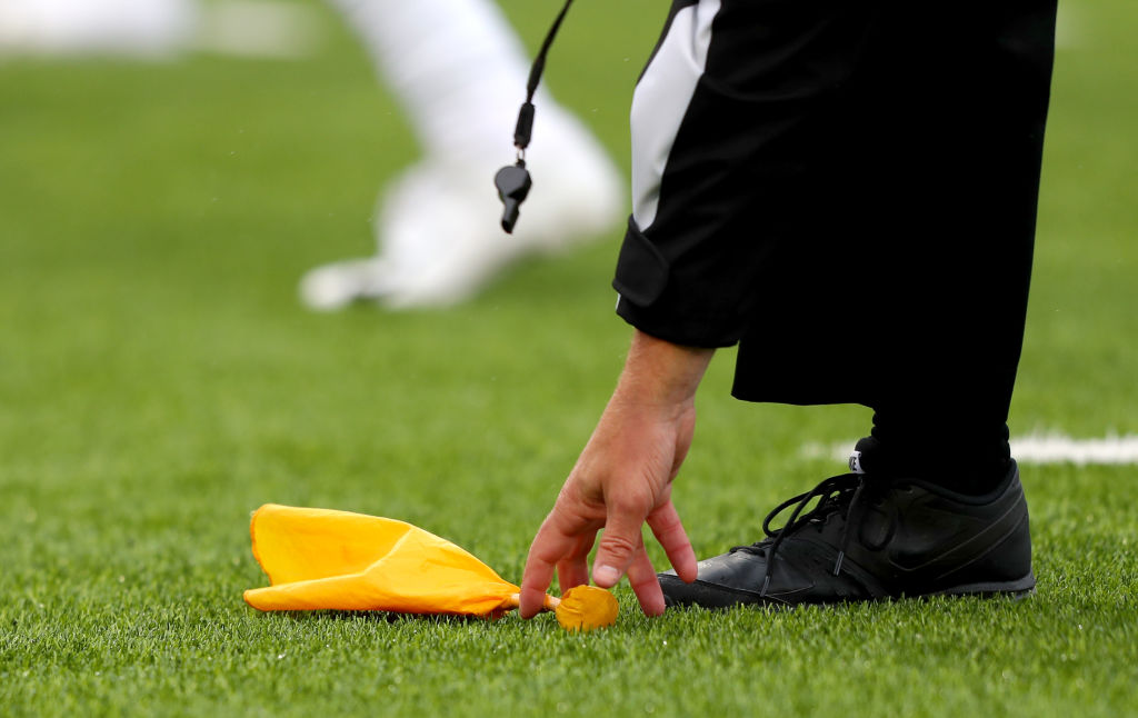 An NFL referee picking up a penalty flag