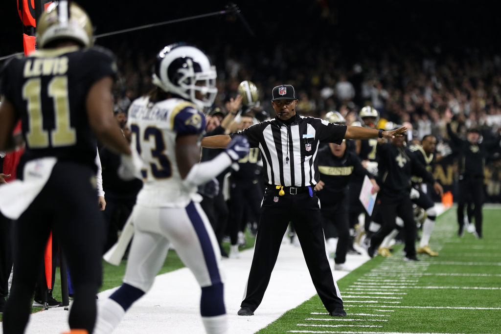 An NFL referee makes a bad incomplete pass call during a game.