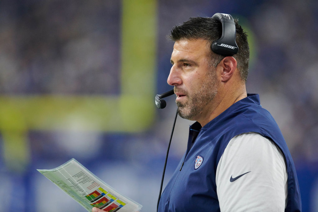 NFL coach Mike Vrabel talks into his headset during a game.