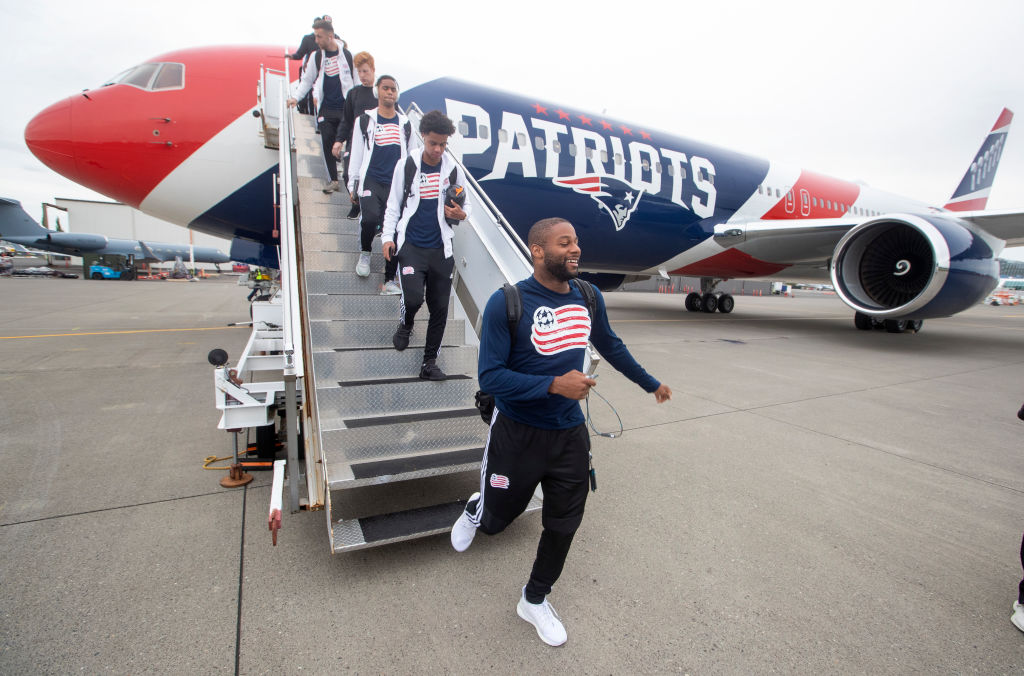 Athletes exit from the Patriots charter plane