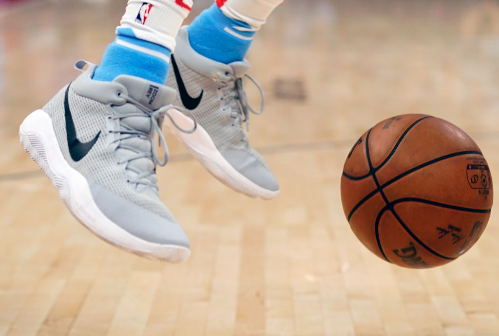A pair of Nike NBA shoes with a basketball next to them.