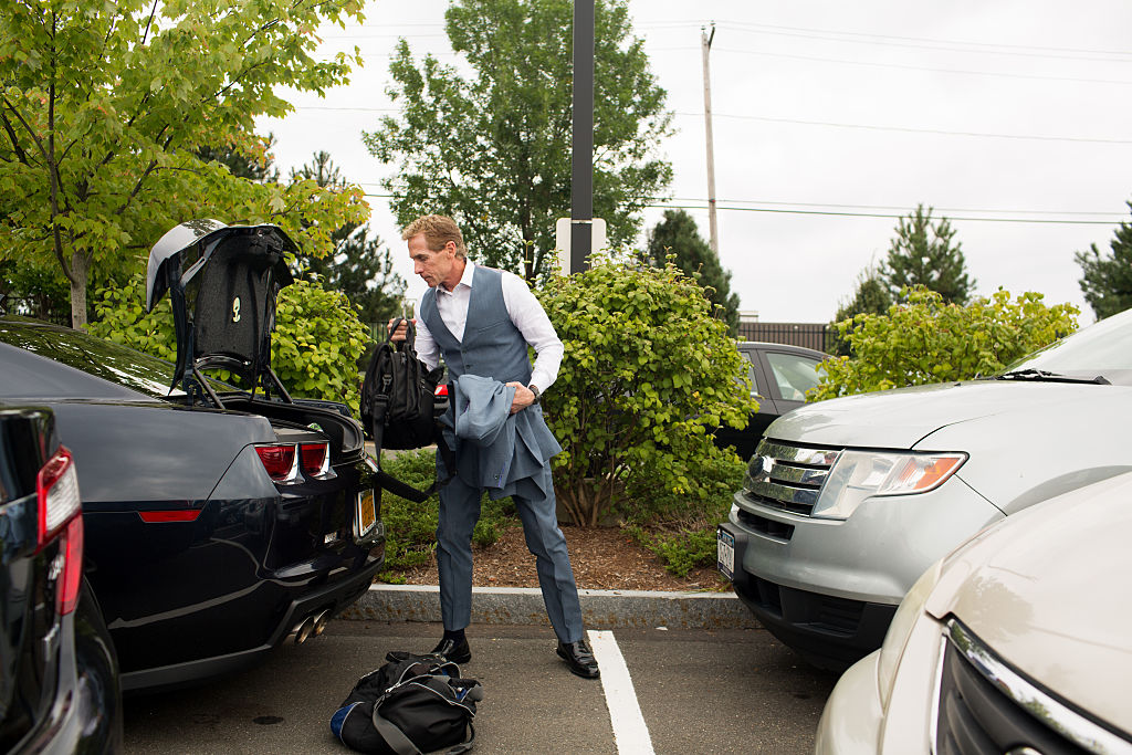 Sports journalist and television personality, Skip Bayless grabs his gym bag from the trunk of his car