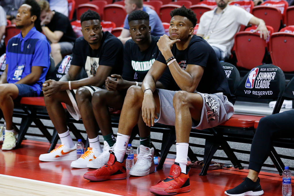 Thanasis Antetokounmpo, Francis Antetokounmpo, and Giannis Antetokounmpo of the Milwaukee Bucks look on during a game