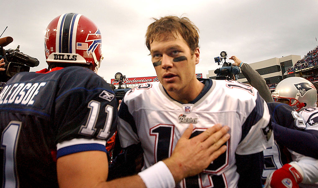 Tom Brady and Drew Bledsoe meet at midfield after a game.
