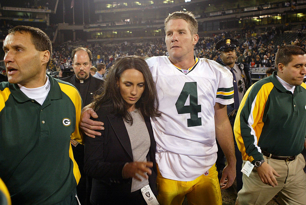 Brett Favre of the Green Bay Packers leaves the field with his wife Deanne after defeating the Oakland Raiders in 2003