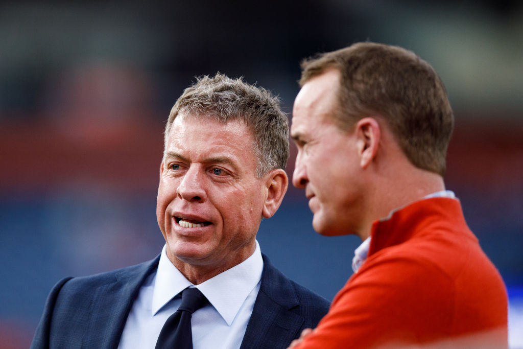 Former NFL quarterbacks Troy Aikman and Peyton Manning chat on the sidelines