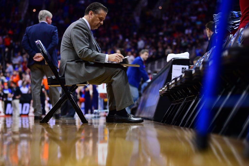 Head Coach John Calipari of the The Kentucky Wildcats writes down plays