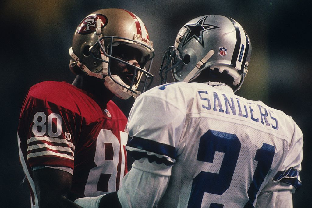 Jerry Rice of the San Francisco 49ers talks with cornerback Deion Sanders of the Dallas Cowboys in 1995
