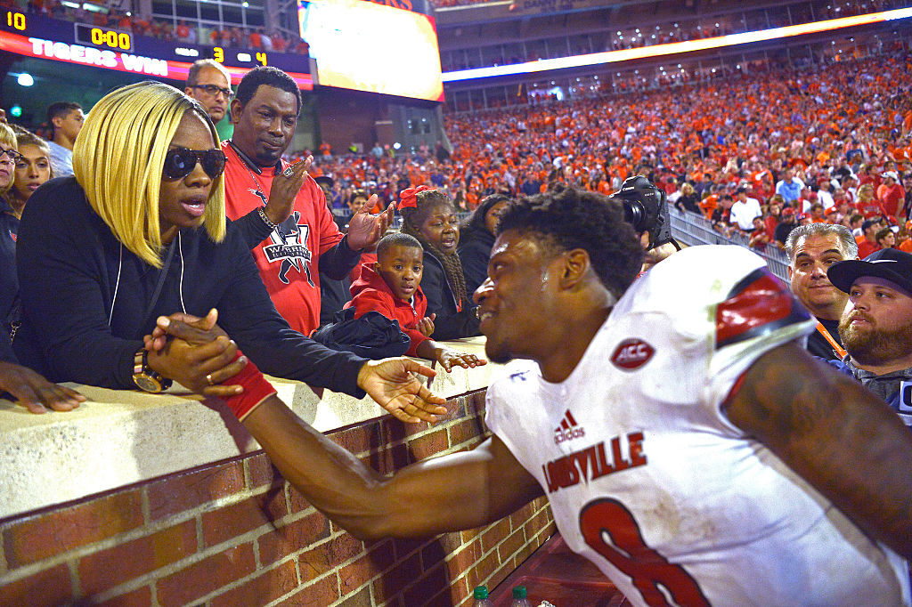 Lamar Jackson speaks with his mother from the field