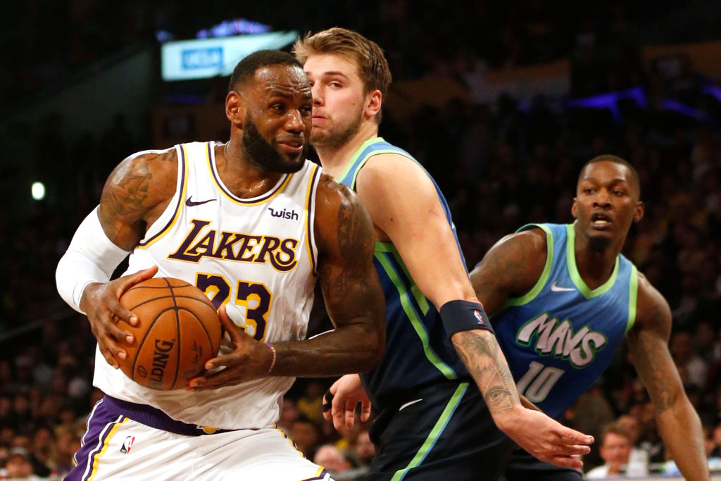 LeBron James drives toward the hoop as Luka Doncic defends