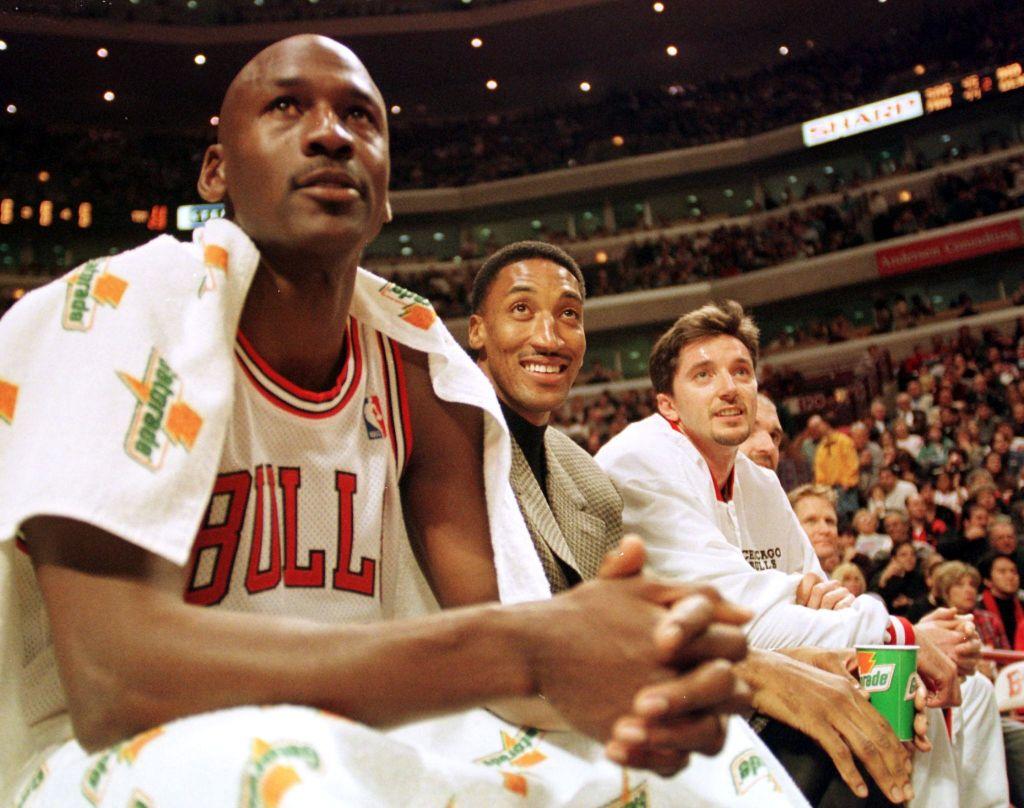 Chicago Bulls guard Michael Jordan (L), injured forward Scottie Pippen (C), and forward Toni Kukoc watch their teammates play