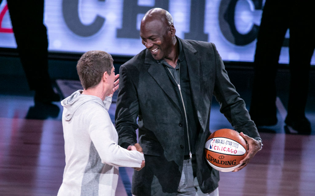 Chicago Bulls President/COO Michael Reinsdorf Jr. accepts the ceremonial All-Star ball from Charlotte Hornets Chairman Michael Jordan in 2019
