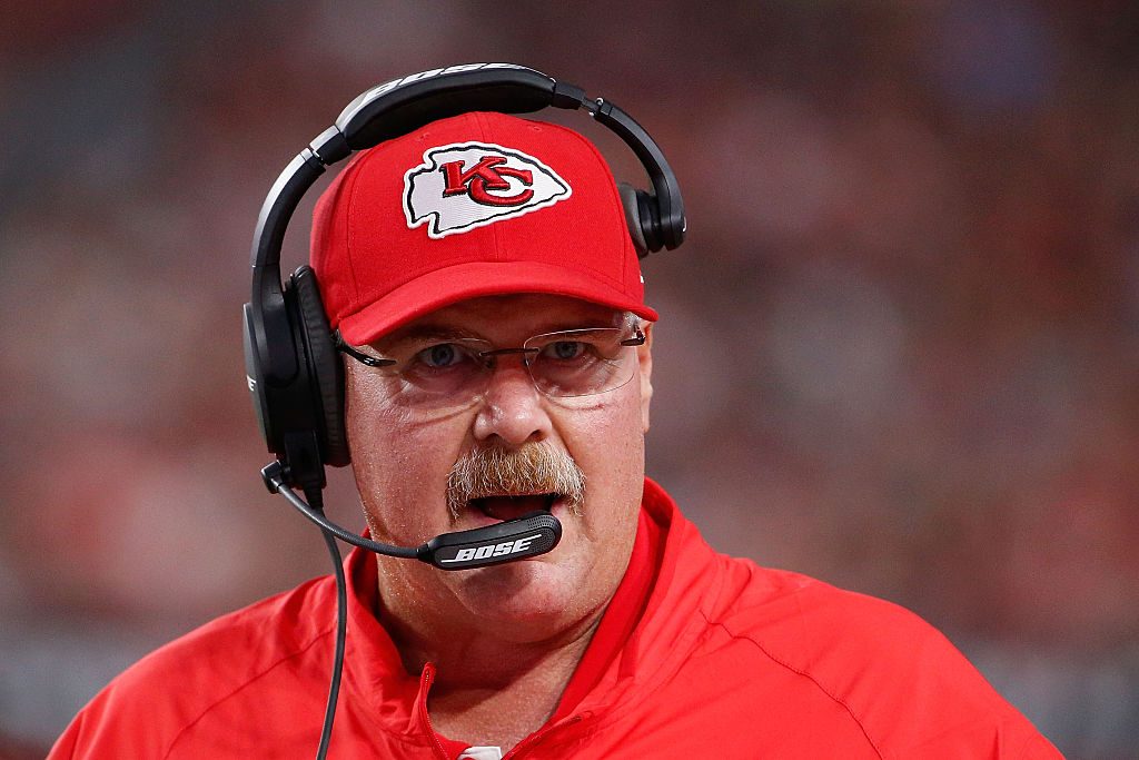 Andy Reid talks into his headset on the sideline