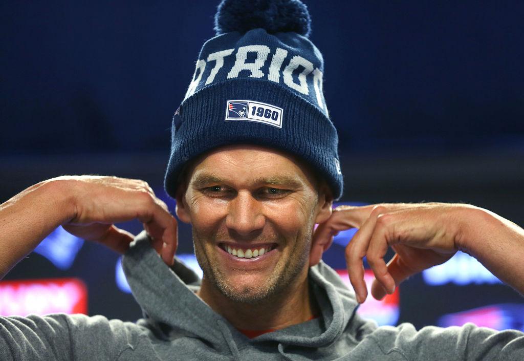 New England Patriots quarterback Tom Brady smiles as he is told by a reporter that former teammate Rob Gronkowski will be an analyst on Fox Thursday Night Football