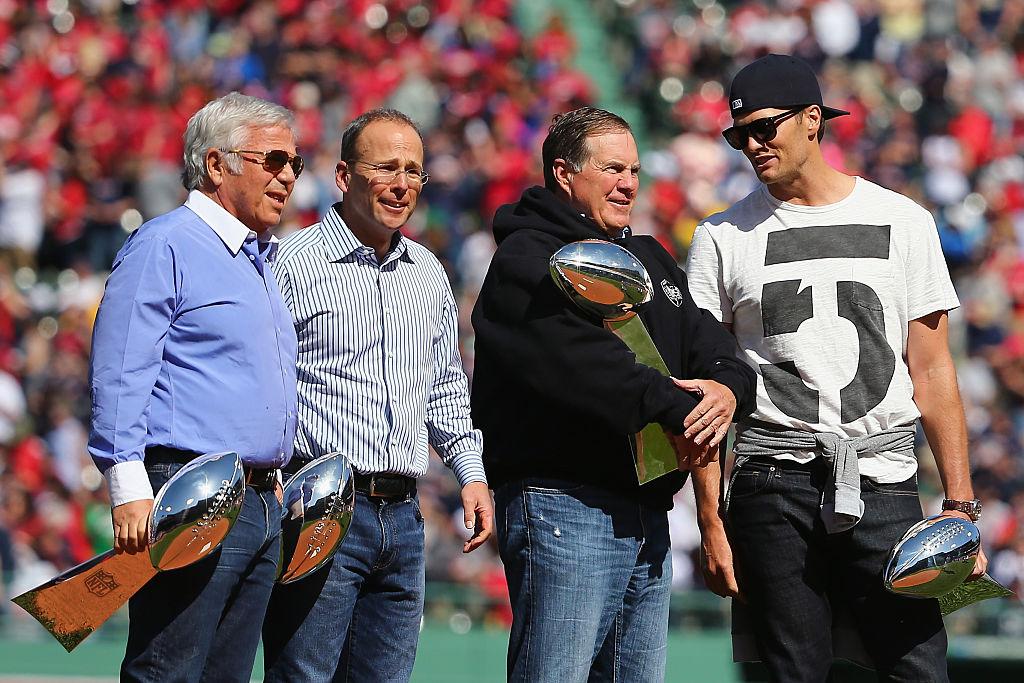 New England Patriots owner Robert Kraft, President Jonathan Kraft, head coach Bill Belichick, and quarterback Tom Brady hold Vince Lombardi trophies in 2015