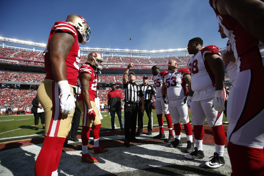 Captains of the San Francisco 49ers and the Arizona Cardinals meet at midfield for the coin toss