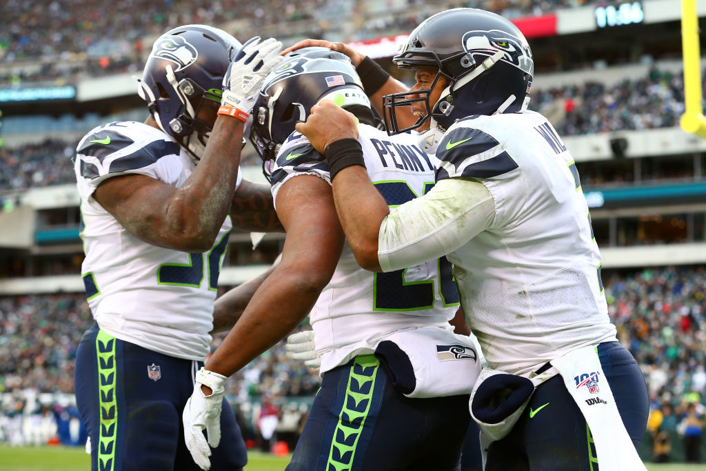 Rashaad Penny of the Seattle Seahawks celebrates with Russell Wilson and Chris Carson