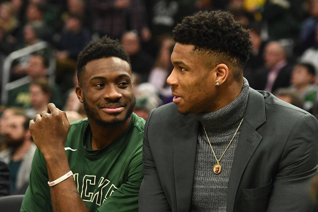Thanasis Antetokounmpo and Giannis Antetokounmpo of the Milwaukee Bucks watch action from the bench