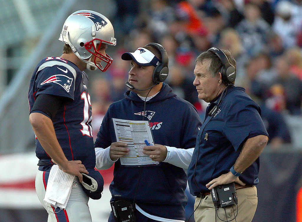 Tom Brady of the New England Patriots confers with Josh McDaniels and Bill Belichick on the sideline